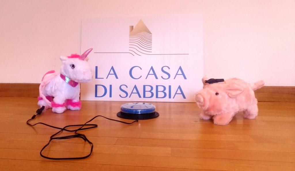 Sulla foto si vedono due giocattoli: l'unicorno e il maialino con il pulsante per attivarli.